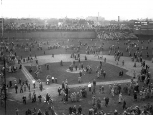 "1929 World Series: Fans depart Wrigley Field via the diamond. Note the temporary bleachers set up beyond the left field wall on Waveland Avenue as well as the ""jury box"" section in left-center field."