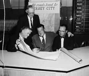 Walter O'Malley: shown  with Jersey City officials, announced that, in 1956 through 1958, the Dodgers would play seven games each season in Jersey City and would have the option to continue the agreement for three years beyond that.