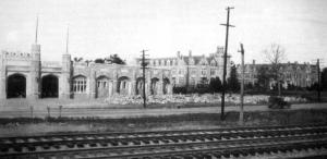Oglethorpe University, 1930s: The granite collegiate gothic Oglethorpe University campus on Peachtree Road outside Atlanta during the Great Depression of the 1930s. From left, Hermance Stadium, Lupton Hall bell tower, and Administration Building. The Southern Railroad is in the foreground.