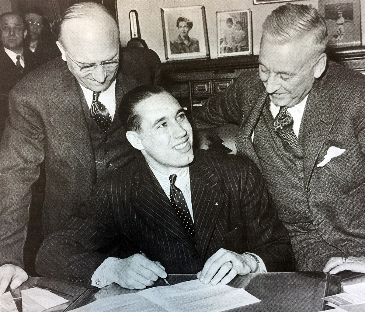 Cleveland Indians star Bob Feller, center, signs his 1941 contract as  general manager Cy Slapnicka, left, and owner Alva Bradley look on.