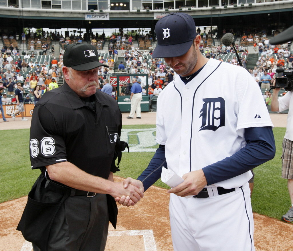 Detroit Tigers' Armando Galarraga, right, and umpire Jim Joyce shake hands the day after Joyce's blown call cost Galarraga a perfect game in 2010 (MLB.COM)
