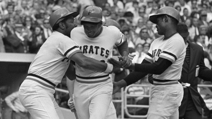 Willie Stargell, left, hugs his Pittsburgh Pirates teammate Al Oliver, center, as Roberto Clemente looks on during the 1971 season. On September 1, 1971, the Pirates fielded an all-Black lineup of African-American and Latino players, a first in the history of Major League Baseball. (MLB.com)