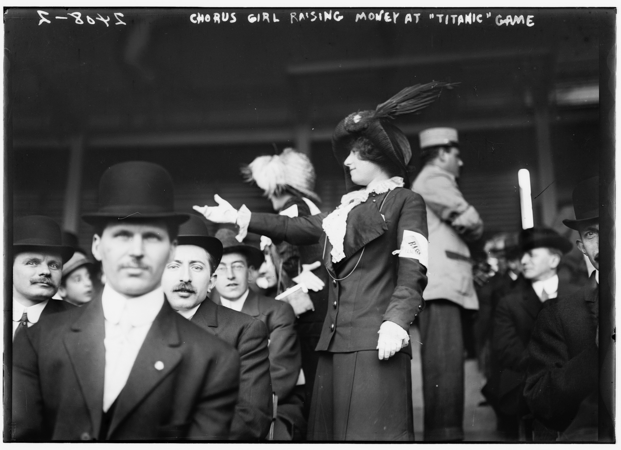 At the 1912 Titanic exhibition game, two members of the Female Giants—a women's baseball team with connections to the New York Giants—roam the aisles to request donations to assist the Titanic's survivors.