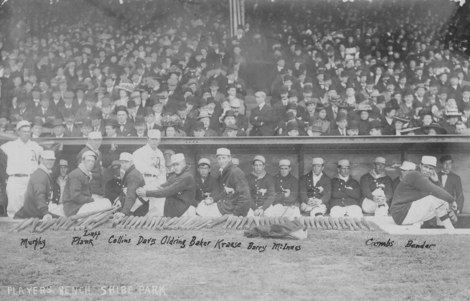 Athletics players relax in their dugout just before the start of the inaugural home opener at Shibe Park on April 12, 1909.