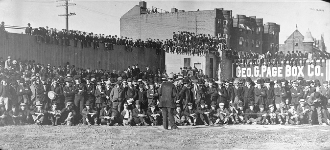 Boston rooters gather in center field, on rooftops, and seated on the outfield fence to see the Boston Americans play the New York Highlanders (Yankees) in a pivotal doubleheader in 1904.