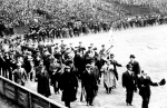 Boston fans march onto the field before a game during the 1903 World Series.